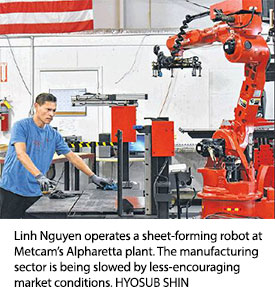 Linh Nguyen operates a sheet-forming robot at Metcam's Alpharetta plant. The manufacturing sector is being slowed by less-encouraging market conditions. HYOSUB SHIN